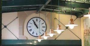 clock on wall next to hanging lights