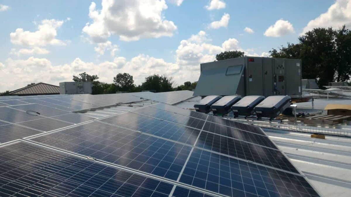solar panels on rooftop of office building with battery units installed nearby