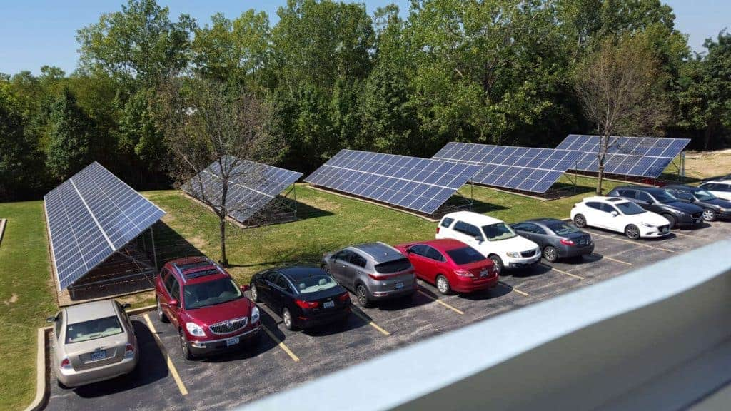 mounted solar panels installed in field next to parking lot