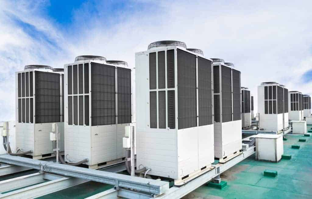 A row of air conditioning units on rooftop with blue sky